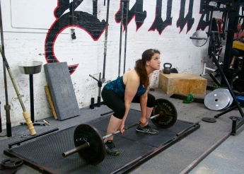 The sumo deadlift begins with the legs in a wide stance, ass down, chest up, with arms grabbing the bar inside the legs.
